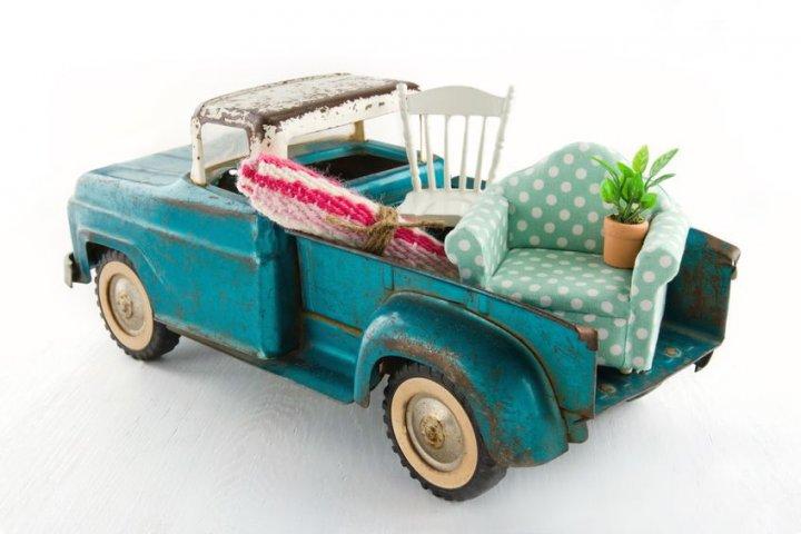 Auszug von zu Hause - Ein türkises Spielzeugauto, welches auf der Laderampe einen Teppich, einen Stuhl, einen Sessel und eine Pflanze geladen hat.