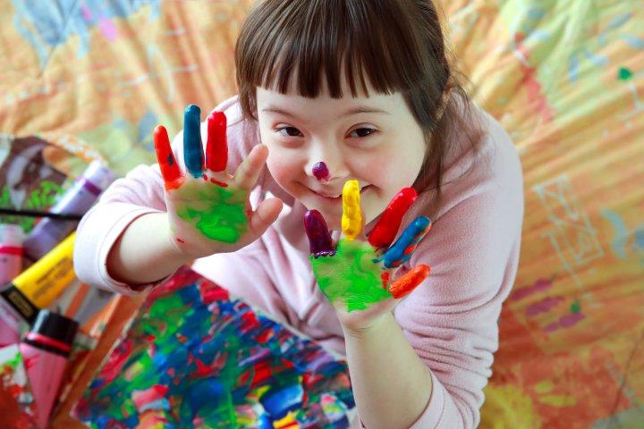 Down-Syndrom - Ein junges Mädchen sitzt auf dem Boden. Auf ihrem Schoß liegt ein bunt angemaltes Papier. Darauf liegen Farbtuben. Sie hält beide Hände mit ausgestreckten Finger nach oben und schaut lächelnd in die Kamera. Ihre Hände sind auch bunt angemalt.