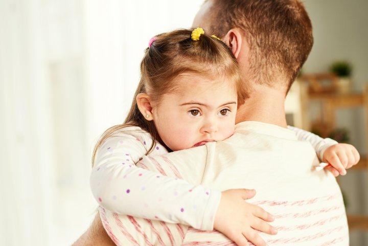Ein Vater hält seine kleine Tochter im Arm. Sie wirkt traurig.