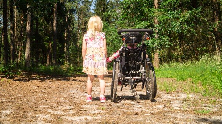 Ein kleines Mädchen und ein Kind im Rollstuhl befinden sich auf einem Weg im Wald. Die Sonne scheint. Sie halten sich an der Hand.