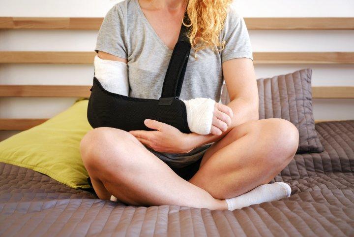 Häusliche Krankenpflege - ein Frau sitzt im Schneidersitz auf einem Bett. Ihr rechter Arm ist eingegipst und in einer Schlinge.