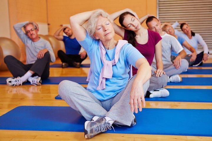 Reha für pflegende Angehörige - Eine Gruppe mit Frauen und Männer sitzt in einem Turnraum auf Matten auf dem Boden. Sie machen gemeinsam Dehnübungen.
