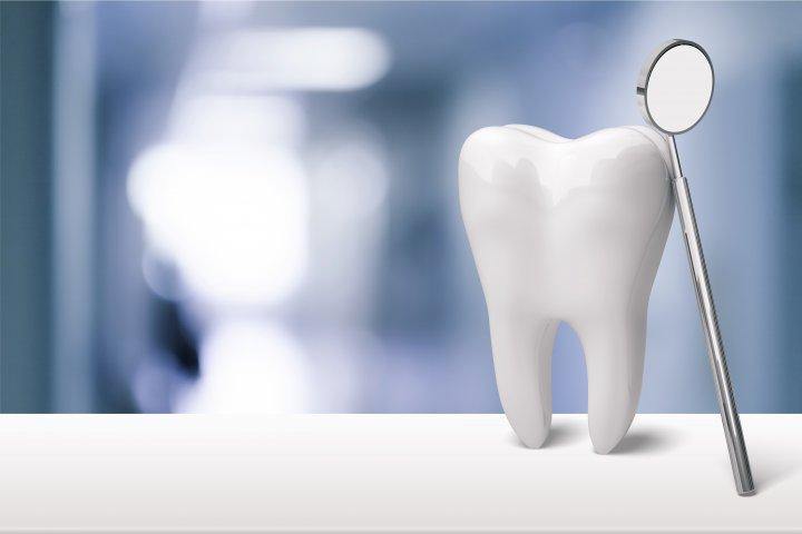 Ein weißer Zahn steht auf einem weißen Untergrund. An dem Zahn angelehnt ist ein kleiner Mundspiegel. Der Hintergrund ist unscharf.