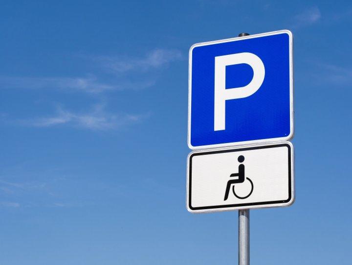 Parkausweis - Ein blaues Verkehrsschild für einen Behindertenparkplatz für Rollstuhlfahrer.