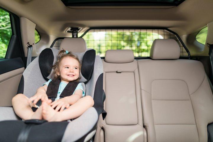 Alles rund ums Auto: Ein kleines Mädchen sitzt in ihrem Kindersitz auf der Rückbank eines Autos. Es lacht und schaut aus dem Fenster.
