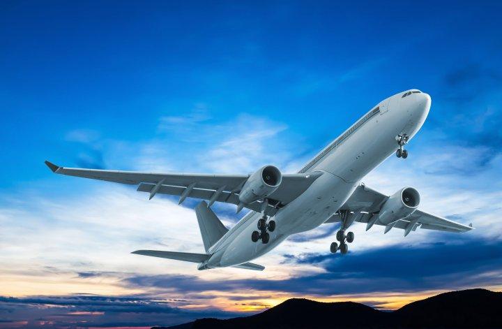 Fliegen: Ein Flugzeug ist gerade gestartet. Im Hintergrund die Abenddämmerung.