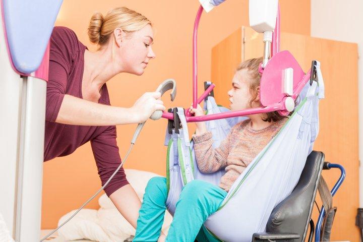 MZEB - Eine junge Frau wird mit Hilfe eines Lifters in ihren Rollstuhl gesetzt.