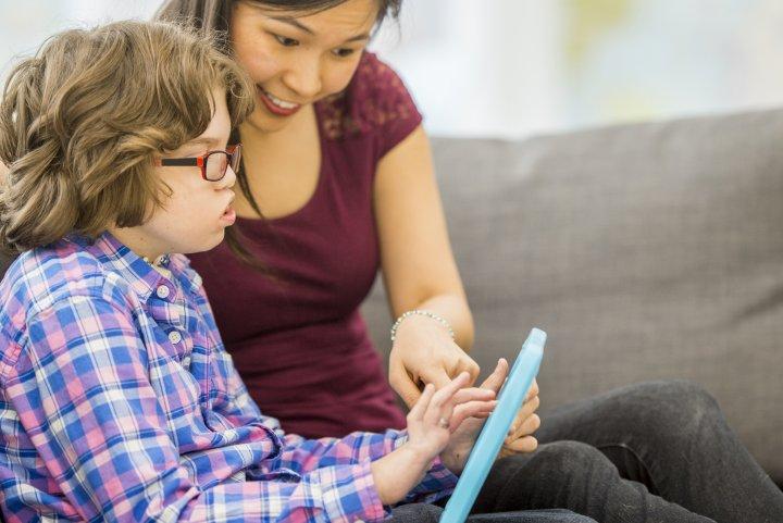 UK - Ein Junge sitzt neben seiner Mutter auf dem Sofa. In der Hand hält er ein Tablet und bedient es. Die Mutter deutet darauf.