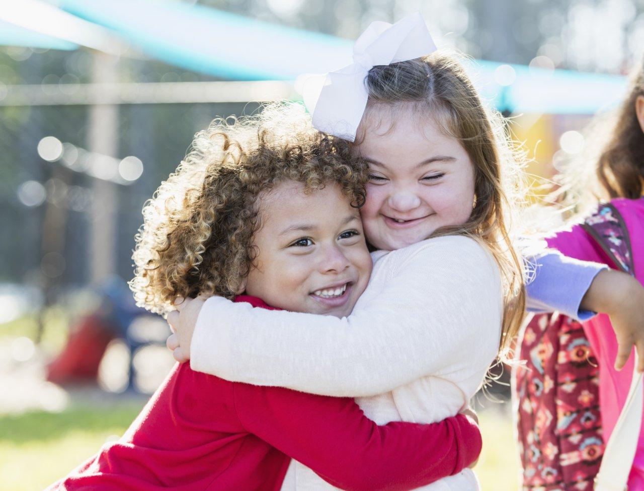 Bild zeigt zwei junge Kinder, die sich liebevoll umarmen.