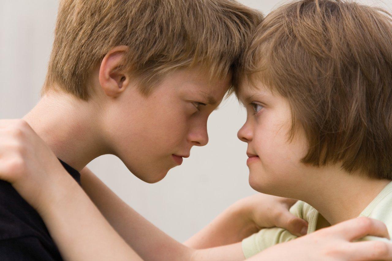 Ein Junge und ein Mädchen stehen sich gegenüber. Stirn an Stirn. Sie schauen sich in die Augen. Die Hände liegen jeweils auf den Schultern des anderen.