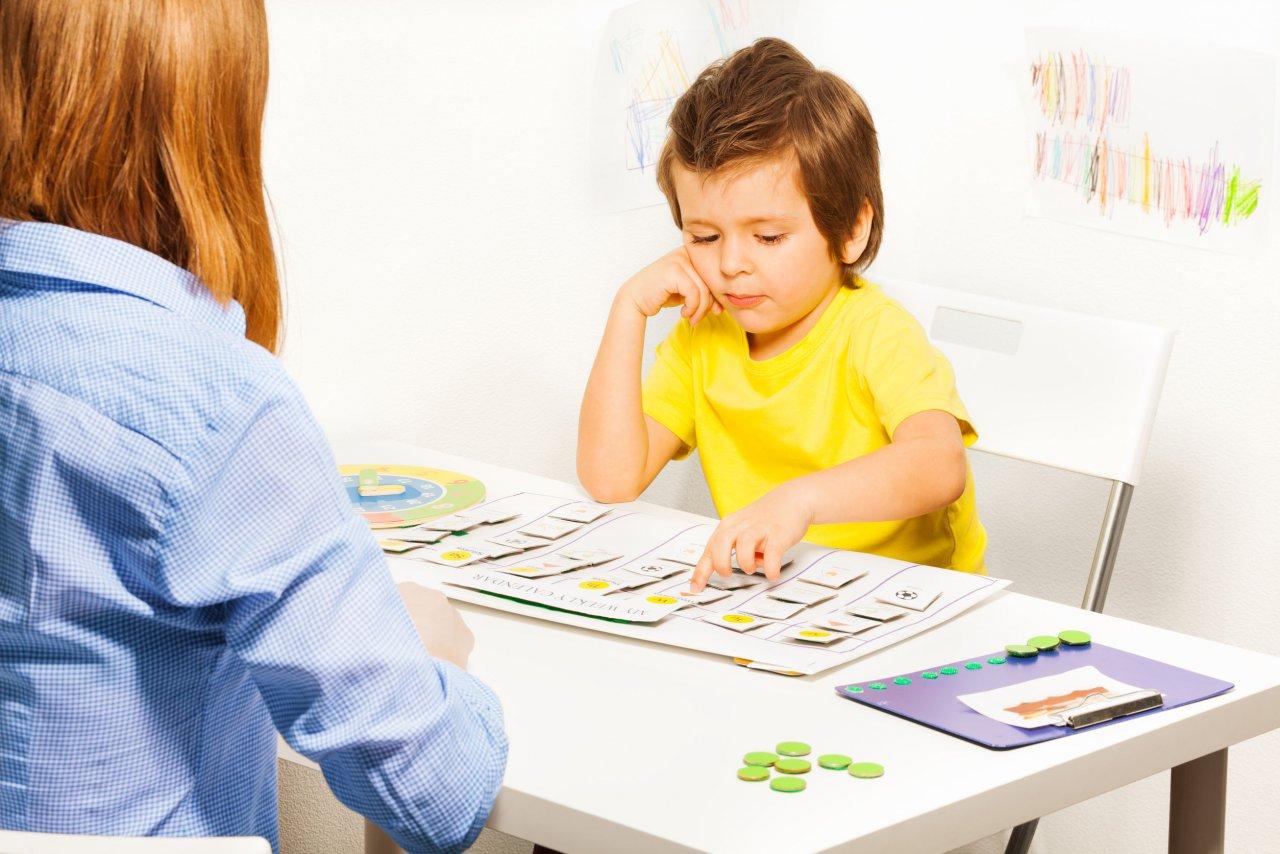 Ein kleiner Junge sitzt an einem Tisch. Vor ihm liegen verschiedene Karten und weitere Arbeitsmaterialien. Mit der einen Hand zeigt er auf ein Kärtchen und mit der anderen Hand stützt er seinen Kopf ab. Ihm gegenüber sitzt eine Frau