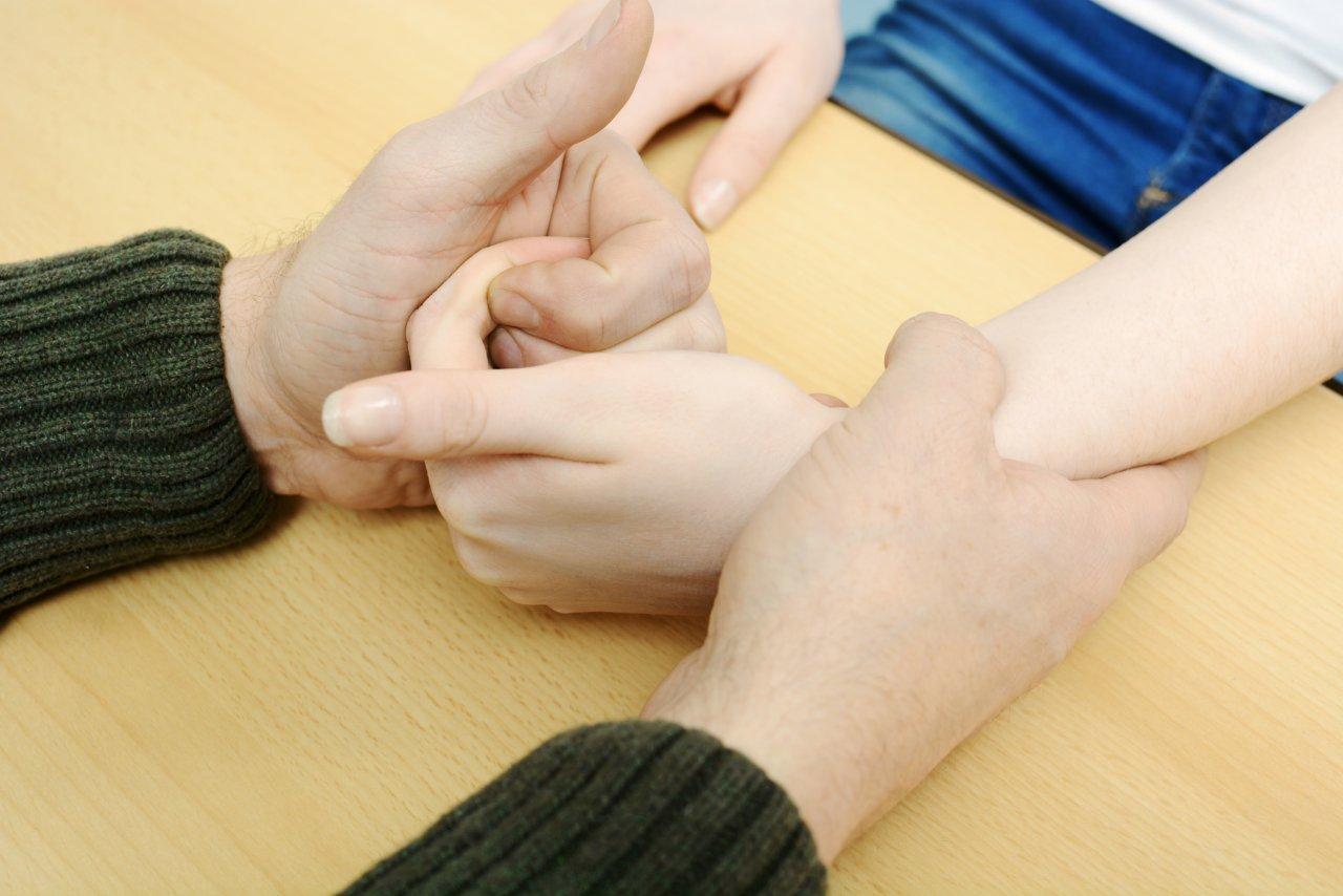 Eine Person hält mit der einen Hand das Handgelenk einer anderen Person fest. Mit der anderen Hand hat sie die Finger der Hand umschlossen. Die Hände liegen auf einem Tisch.