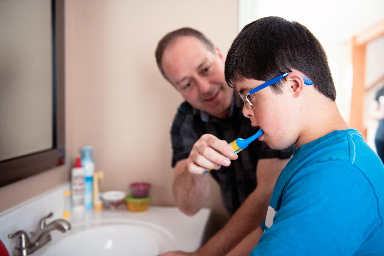 Ein junger Mann steht im Bad am Waschbecken und schaut vor sich in den Spiegel. Ein Mann steht neben ihm und putzt ihm die Zähne. Er lächelt freundlich.
