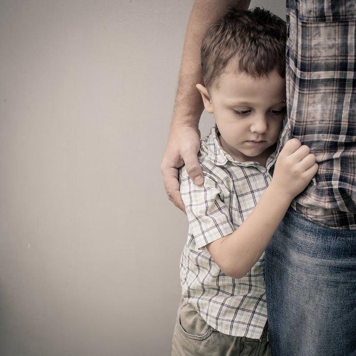 Ein kleiner Junge steht neben einem Mann, er hält das Hemd des Mannes mit einer Hand fest und lehnt sich an ihn. Der Junge hält den Kopf gesenkt. Er wirkt traurig. Der Mann hat den Arm um den Jungen gelegt.